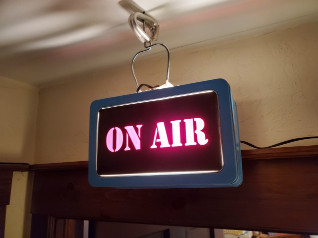 Shows a make-shift 'on-air' light of the kind you would find in a news radio booth to indicate the host is live on air.